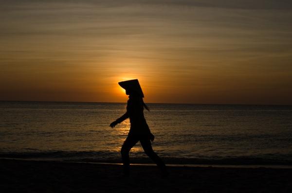 une silhouette d'une femme en chapeau traditionnel sur la plage Vietnam